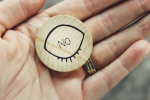 "hand holding a wooden token that reads ""no"""